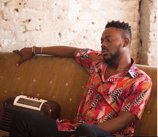 Adekunle Gold sitting beside a radio